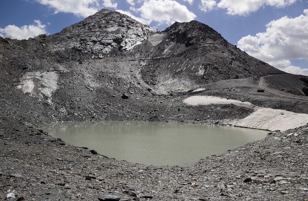 Noch vor zehn Jahren war die Mulde, in der sich heute der See befindet, weitgehend mit Eis gefüllt, so dass man vom Liftausstieg her problemlos in den Hang queren und geradeaus über den (so nicht vorhandenen) See abfahren konnte, ohne am anderen Ende aufsteigen zu müssen. Mehr noch, genau in Blickrichtung dürfte vor 1995 der TK de Glacier de Bellecôte verlaufen sein, höchstwahrscheinlich auf einem gleichmäßigen Gletscherhang.